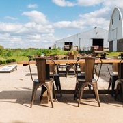 patio with wooden table and industrial chairs barn in background