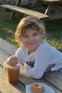 young girl enjoying a cider donut and sider slush