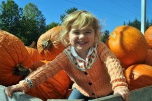 young girl smiling in a bin of pumpkins