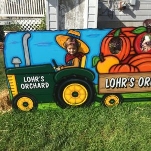 young girl poking her head through a tractor photo prop