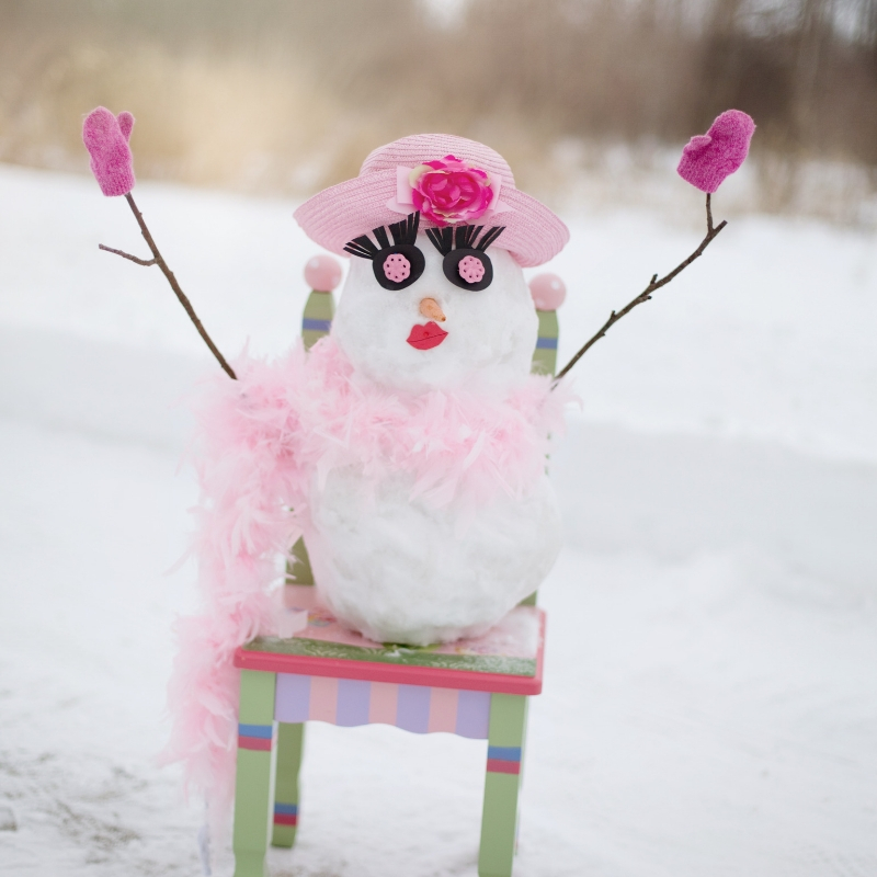 snow woman with pink hat on whimsical chair
