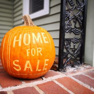 pumpkin on porch with home for sale carved into it